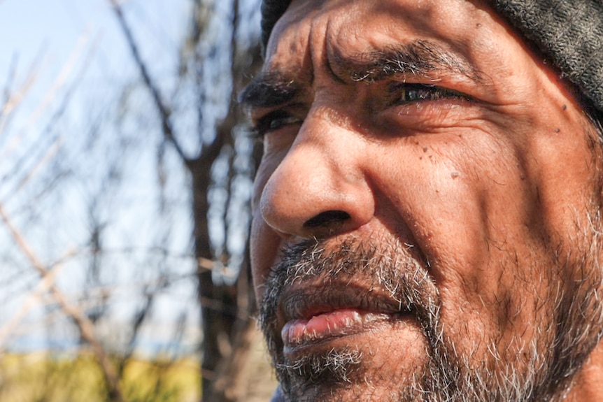 Close up of Warren Foster with the dappled shadow of a Melaleuca tree on his face