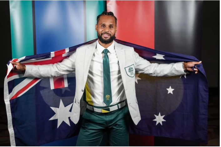 Patty Mills in his Olympic uniform holding the Australian flag
