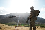 SAS soldier overlooks valley in Afghanistan as Black Hawk helicopter flies past in 2012.
