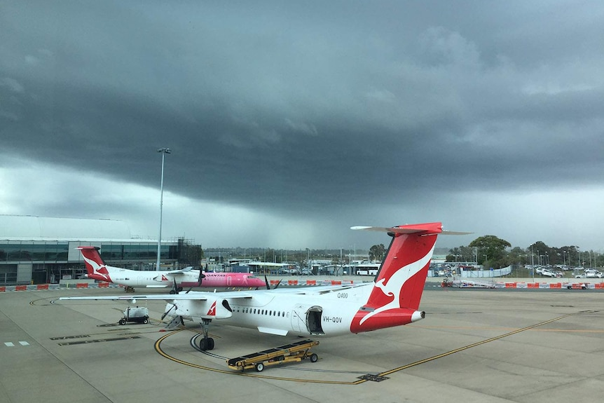 Planes on the tarmac at Brisbane airport with storm clouds on November 7, 2017.