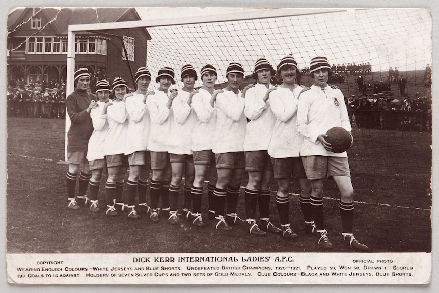 A black and white picture of a women's football team wearing white shirts and black and white hats in front of a goal