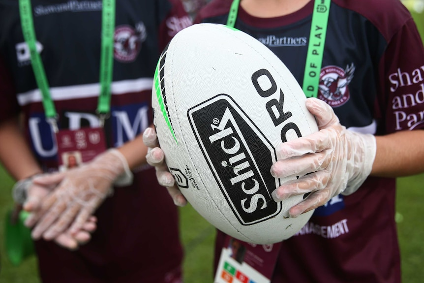 A ball boy holds an NRL rugby league ball while wearing a pair of gloves.