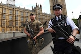 A soldier and police officer walk past UK's Houses of Parliament.