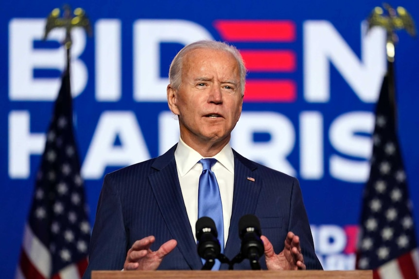 Joe Biden gestures with both hands while speaking at a lectern. He is between two flags and a sign that reads BIDEN HARRIS
