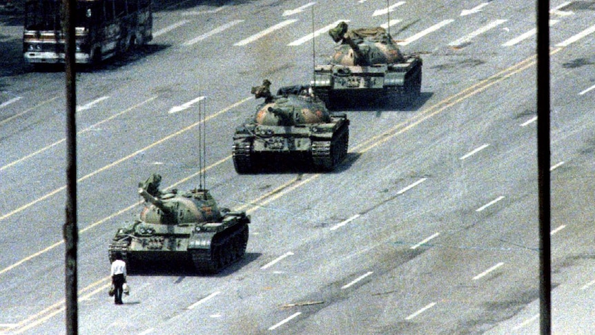 A man stands in front of a row of tanks