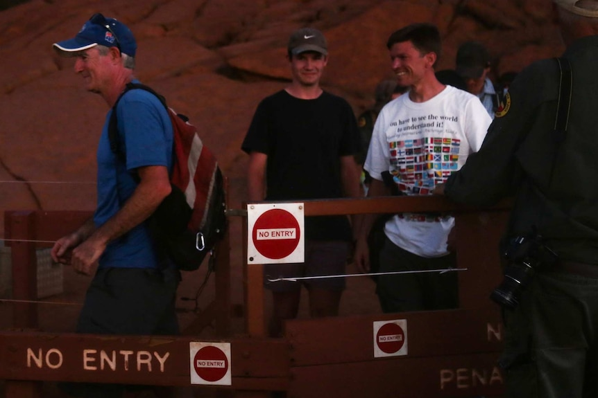 Three white men of varying ages smile as they walk away from Uluru.