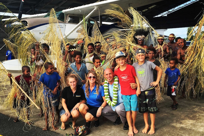 Mark Palm and his family are surrounded by traditionally-dressed locals in front of a float plane