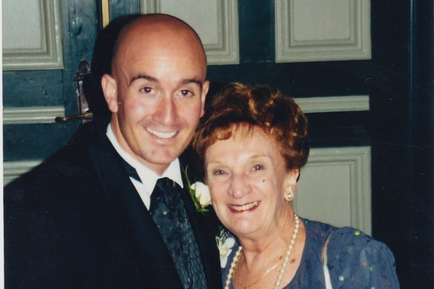 Simon Kennedy, dressed in formal suit, with his arm around his mother, Yvonne, in formal purple dress. Both are smiling widely.
