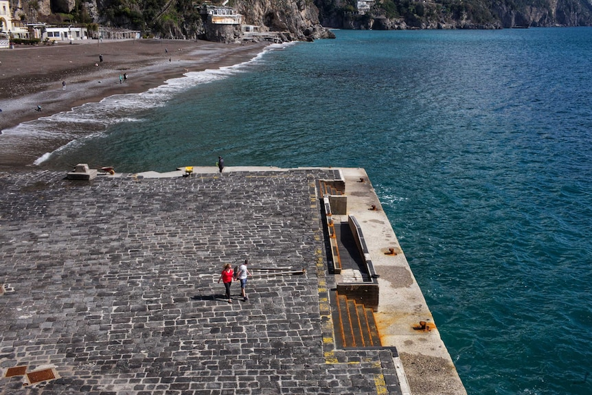 A couple walk along a dock on Italy's Amalfi Coast.