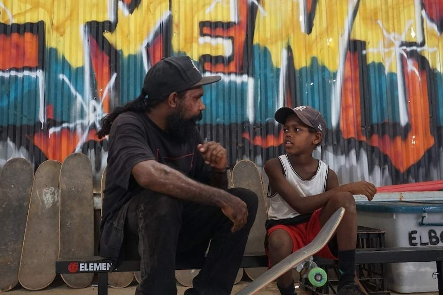Nicky Hayes speaks to nine-year-old Ruot Flowers who holds a skateboard.