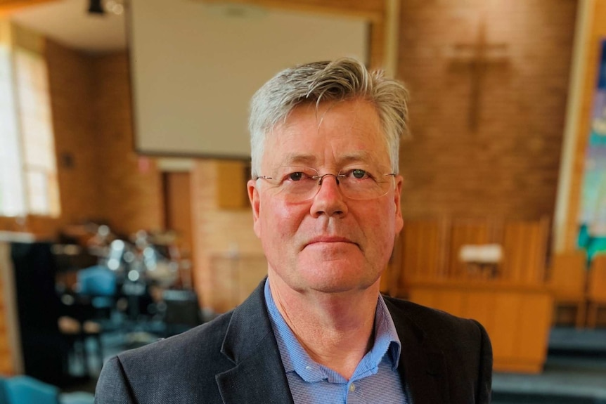 Man with glasses stands in church