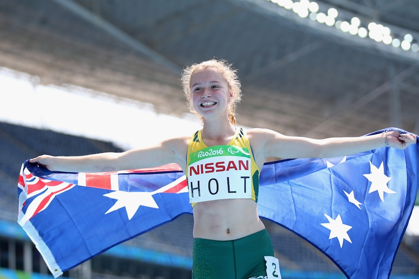 A female Paralympian smiles at the camera while posing with the Australian flag after winning a silver medal in Rio.