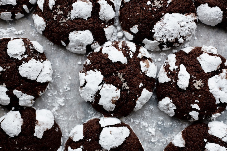 Close-up of a batch of dark chocolate crinkle cookies, a delicious dessert.