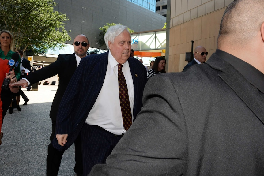 Businessman Clive Palmer, flanked by security guards.
