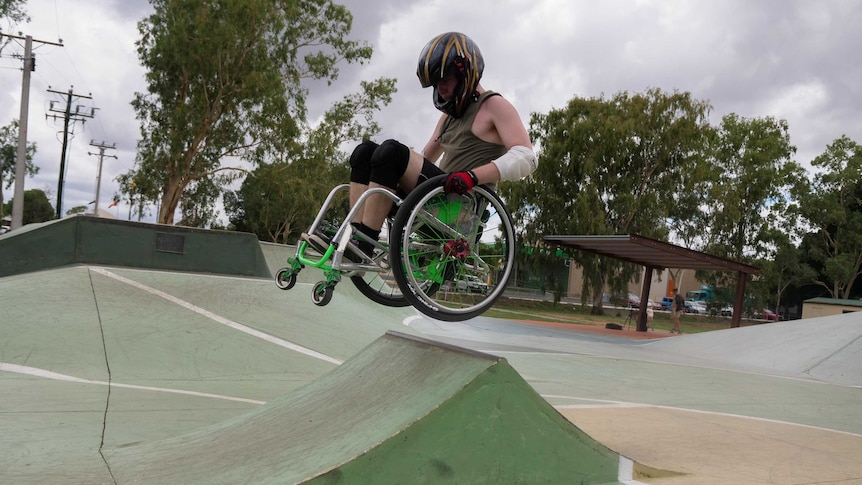 A man in a wheelchair gets air on a ramp. He is wearing a motorbike helmet and elbow guards.