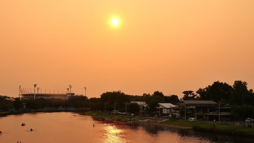 An orange-tinged view of the sun over the Yarra River taken from Princes Bridge facing East.
