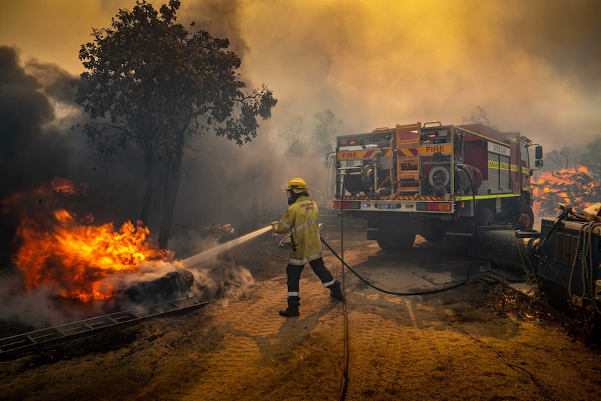 A DFES firefighter tackles flames with a hose at King Road during the Oakford Bushfire
