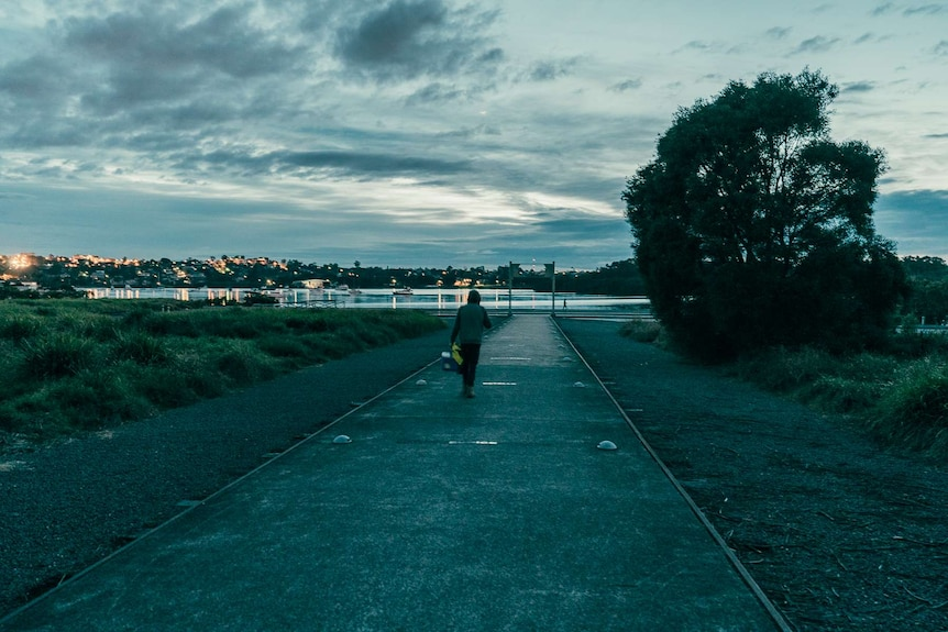 Louis Giles walking to walking towards a bay to work at dusk with an esky in hand.