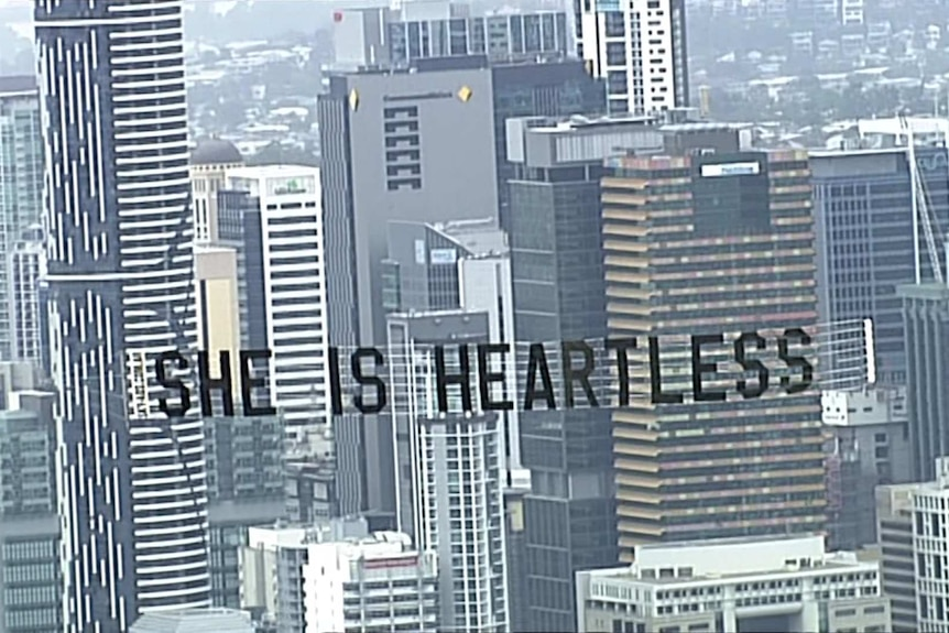"""Banner says """"she is heartless"""" seen over Brisbane sky line."""