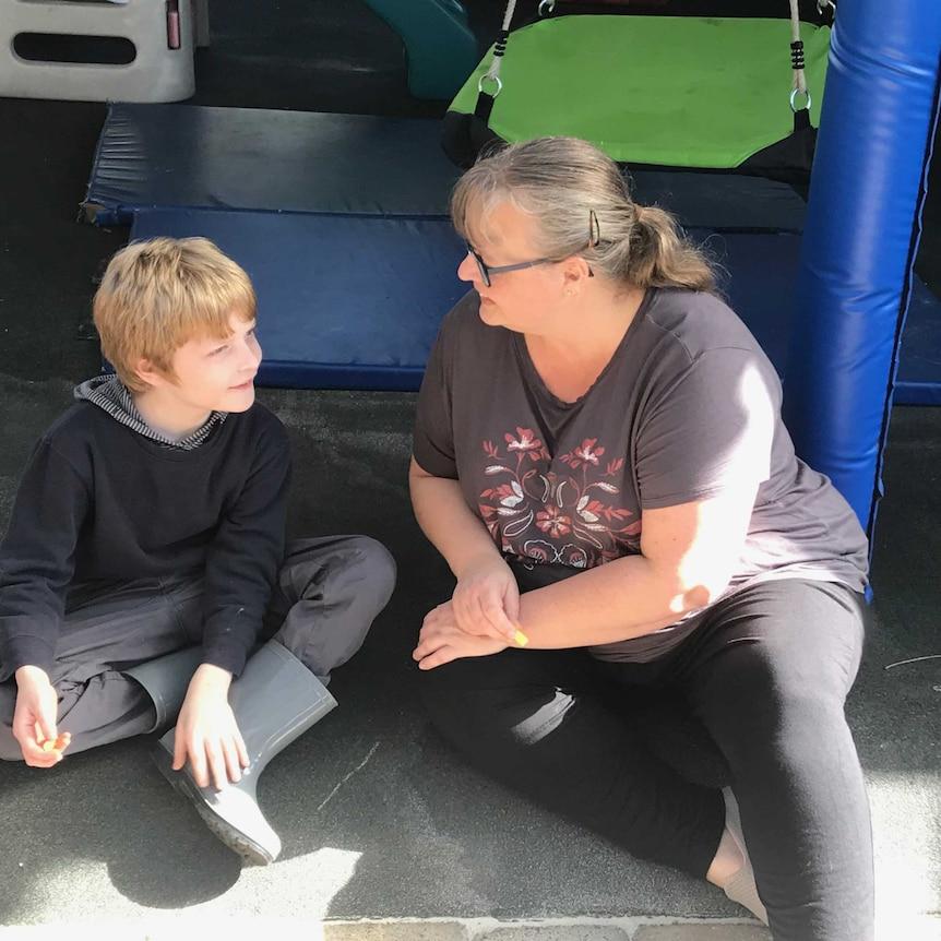 Martina McNeill smiles with son Alex sitting near a playground.