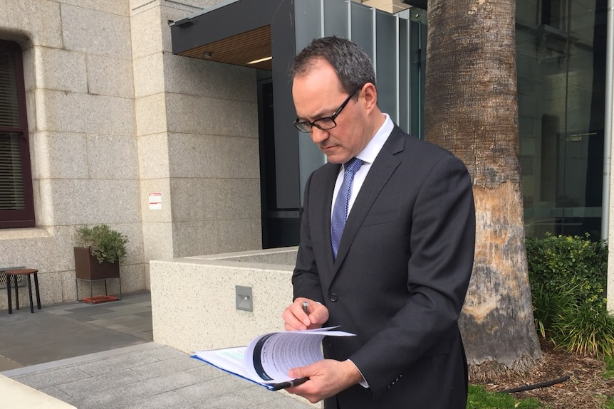 Liberal MP Corey Wingard looks down at paperwork.