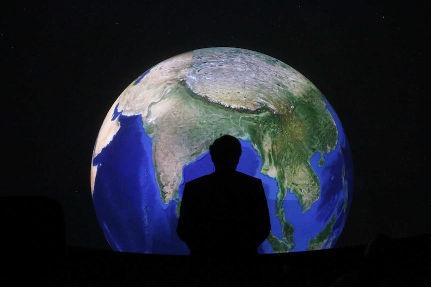 Sagoma di un uomo in piedi da un globo.