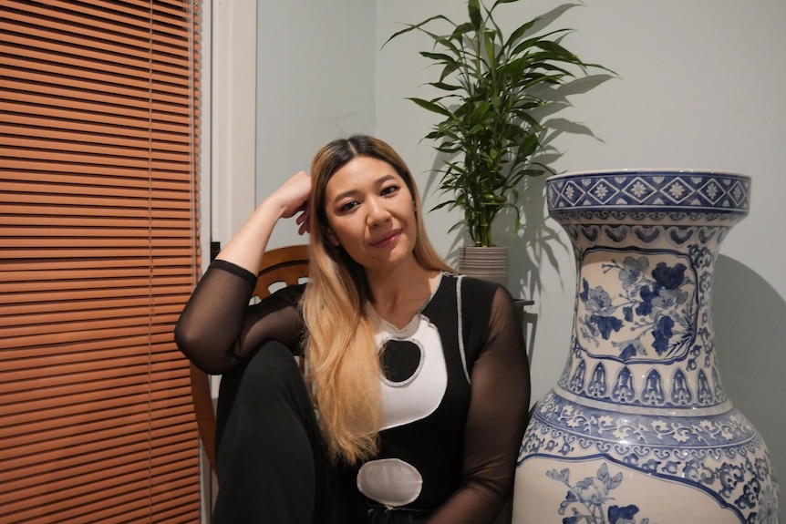A person sits and looks to the camera with a blue and white vase to their right, and a plant behind. They wear ying yang shirt.