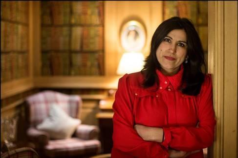 Jasvinder Sanghera standing in a doorway of warmly lit room, arms crossed, smiling a little.