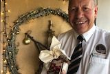 A man in a shirt and tie smiles in front of a Christmas wreath adorned with lights while holding a packaged Christmas pudding.