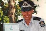 A police officer poses with a certificate