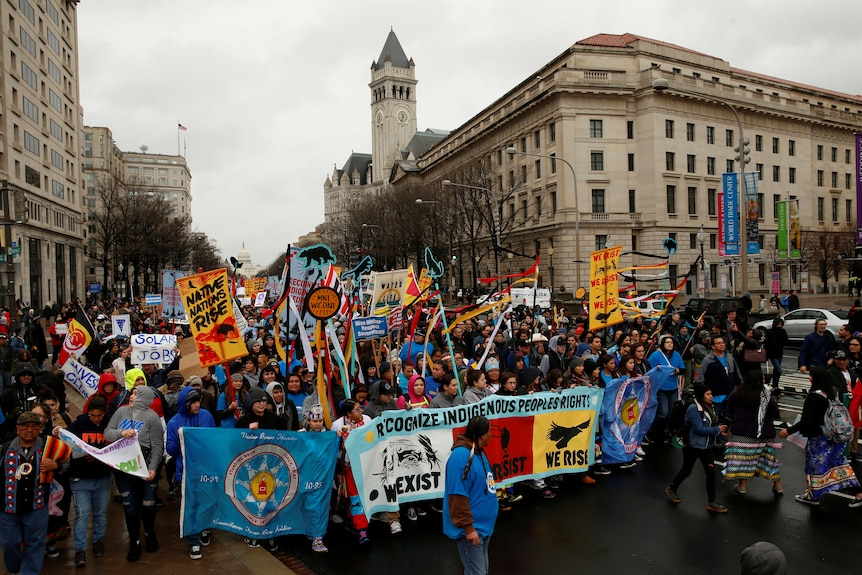 Large groups of people march while carrying colourful flags protesting Keystone XL in the streets of Washington, United States.