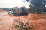 A dozer makes its way through floodwaters at Broken Hill.