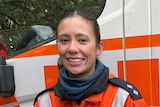 Jess Rice, wearing an orange SES uniform, in front of an SES truck.