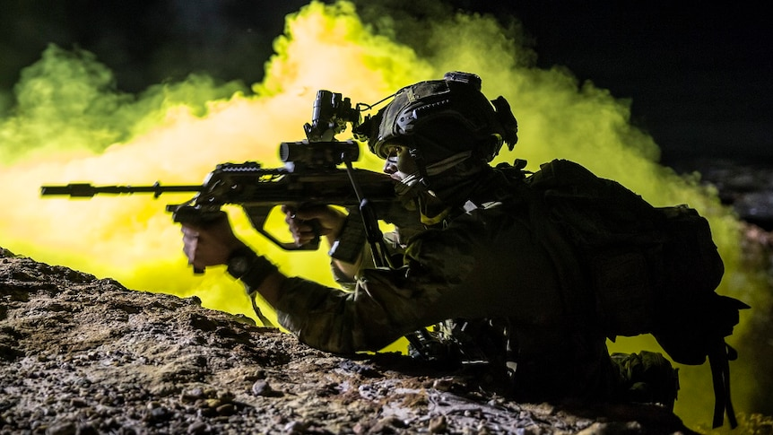 Silhouette of fully armed Australian soldier at night with smoke in backdrop