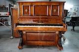 A tan-coloured piano in a warehouse.