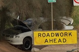 A white sedan crashed into a tree with a yellow roadwork ahead sign in front of it