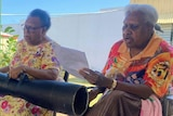 Three elderly women sit on chairs singing while one also plays a traditional hand drum