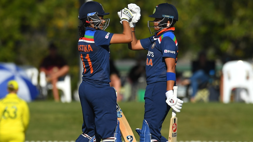 Yastika Bhatia and Shafali Verma high-fove each other while on the field, wearing their batting gear