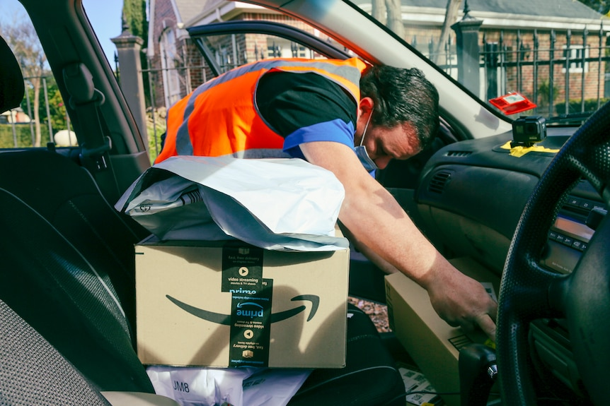 A man in an orange high-vis vest bends over to reach a package in the foot well on the passenger side of his car.