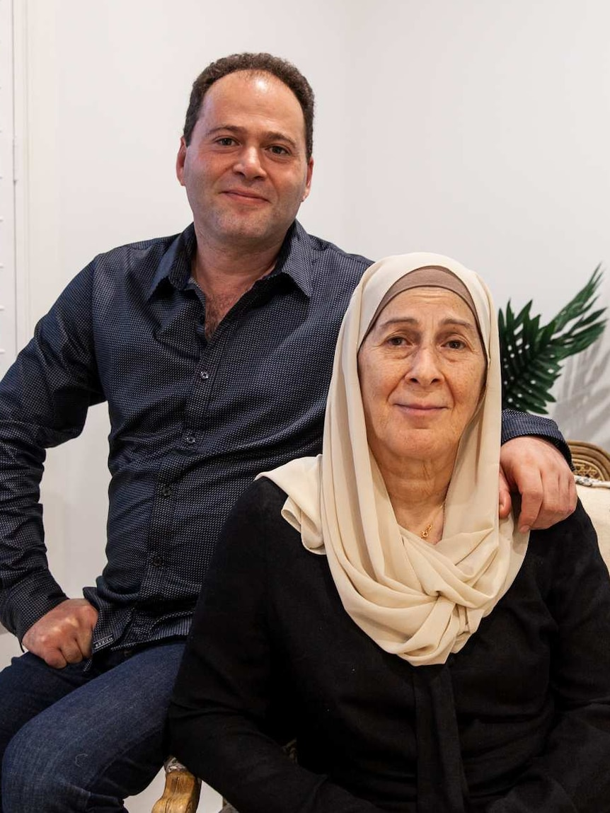 You view a middle aged man leaning against a chair, with an elderly woman in a Hijab sitting next to him.