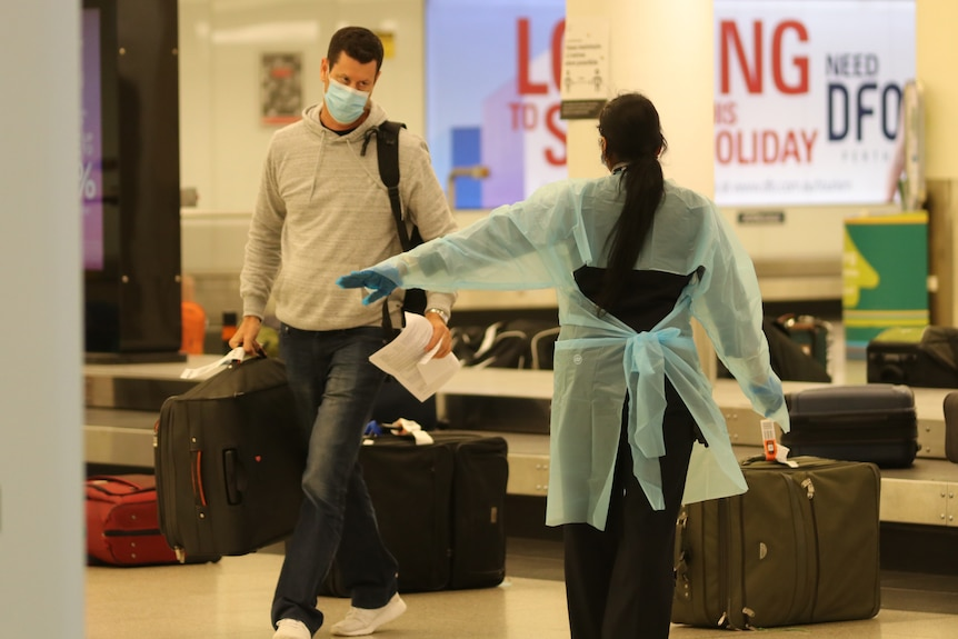 A man wearing a face mask and carrying luggage is directed by a woman in PPE near a baggage carousel at Perth Airport.