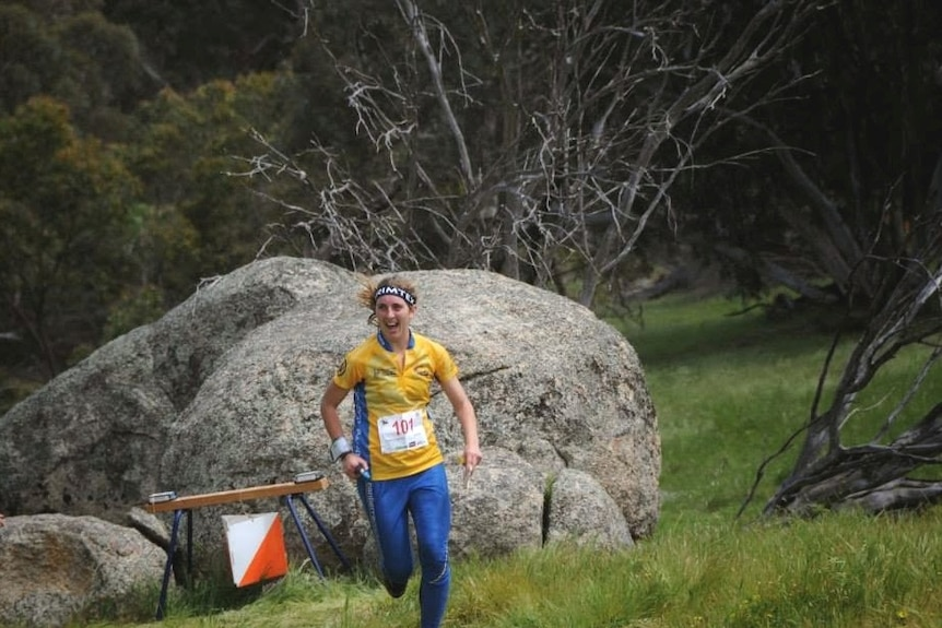 Orienteer resumes running after signing off at the final course checkpoint in front of a larger boulder