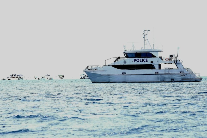 A police search boat floating on the sea with other boats on the horizon.