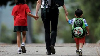 A mother walks holding the hands of two children on their way to school holding backpacks.