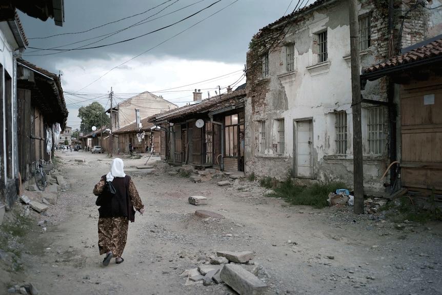 A woman walks down a dirt street edged with houses in disrepair.