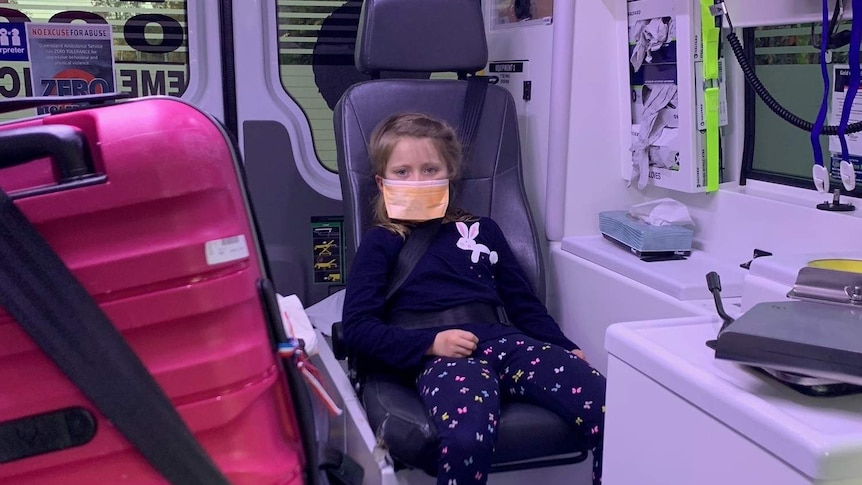 Six-year-old girl sits in ambulance with a face mask over her face.