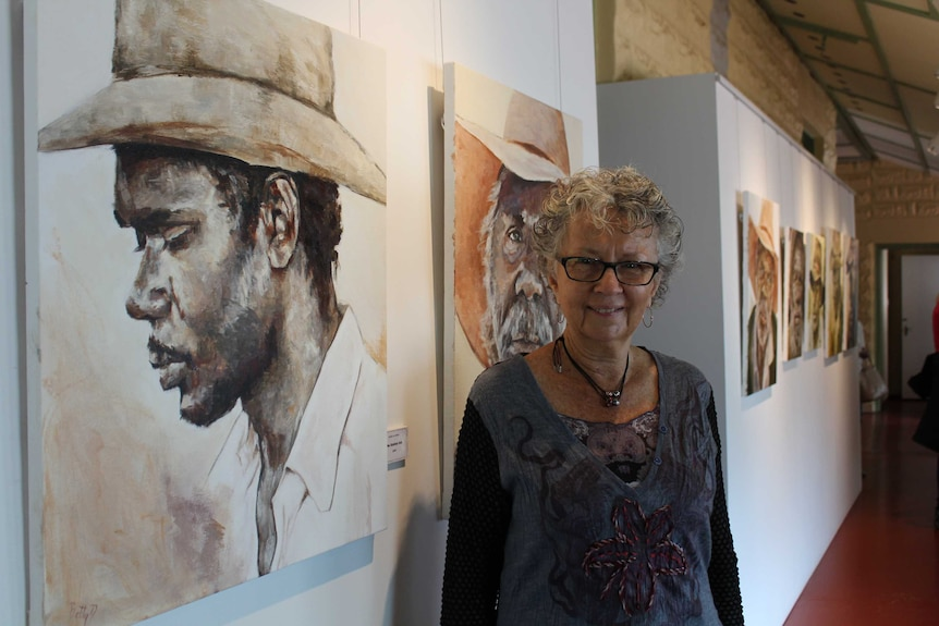 Artist Betty Davies stands in front of a row of paintings of aboriginal stockmen and their hats