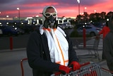 A man in a mask and protective suit stands next to a shopping trolley as the sun rises behind him.