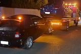 A blue sedan on the back of a flat-bed tow truck with another black hatchback being towed behind