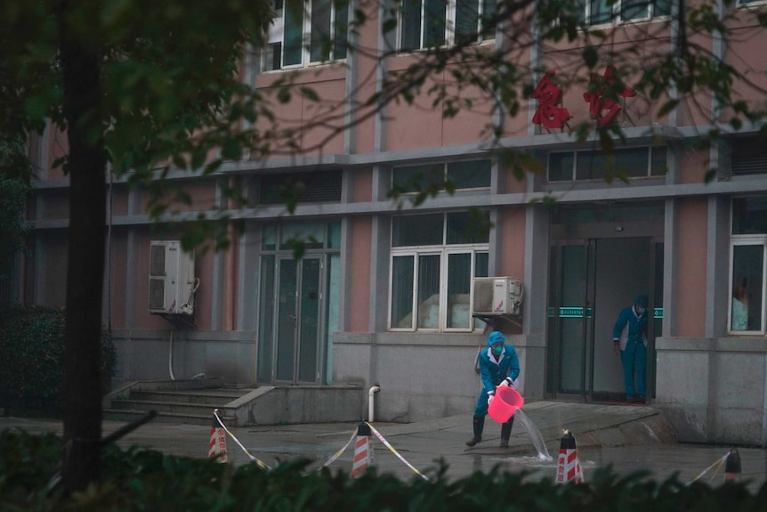 Hospital staff wash Wuhan hospital entrance, using a bucket and wearing protective clothing.